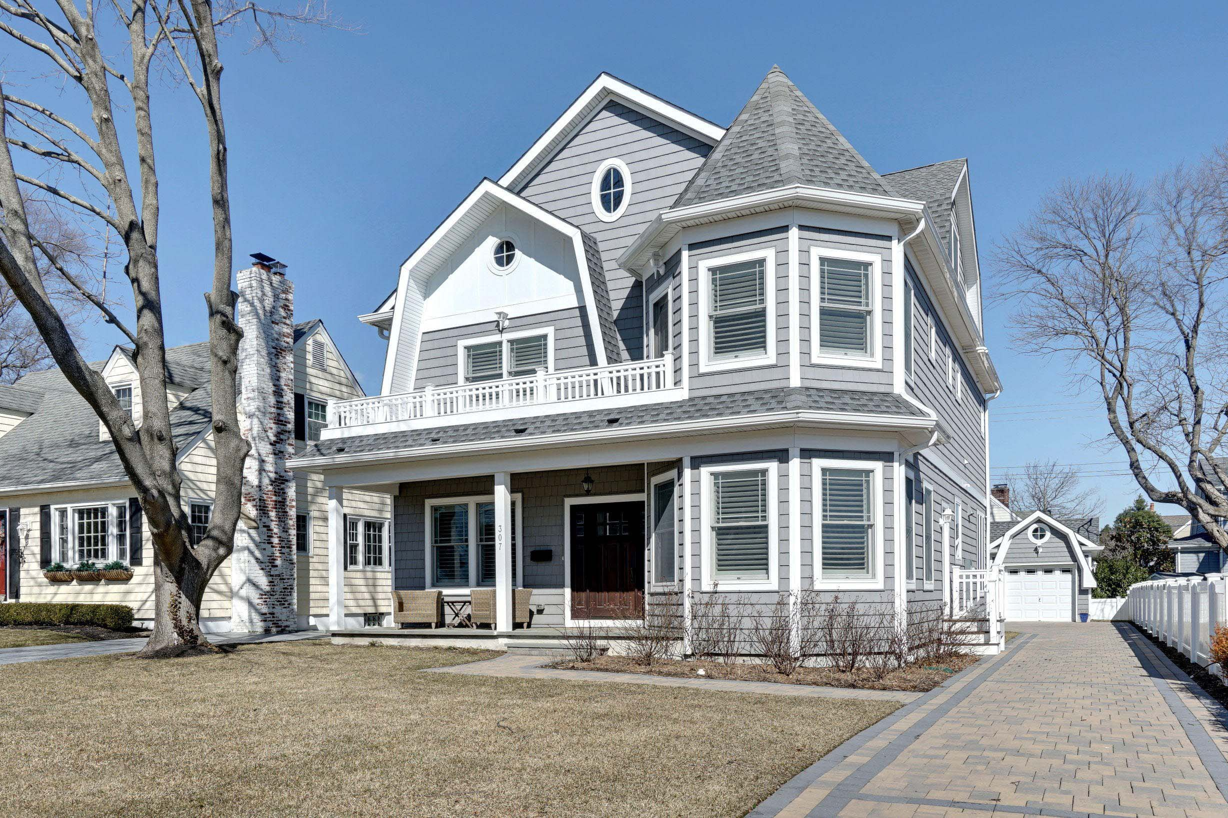 Gray viny siding color with white trim and wall paneling. Dark brown stained wood front door. White railings. Gray shingled roof. Paver driveway. Gray decking.