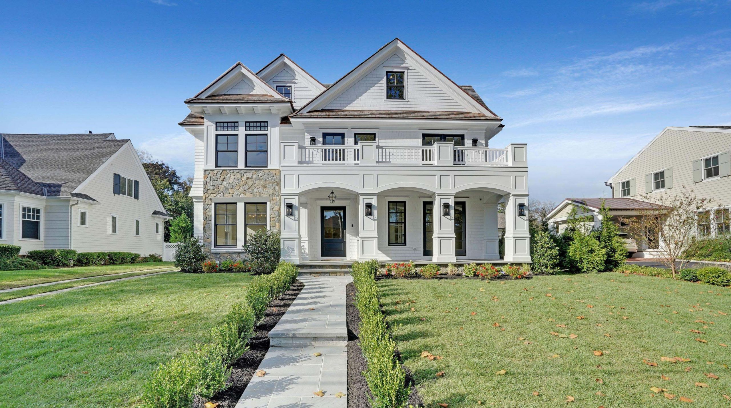 White siding colors with thick white trim and wall paneling. brown shingled roof. Brown stone veneer. Blue front door with tapered porch columns and white rails. Black framed windows. Blue stone walkway.