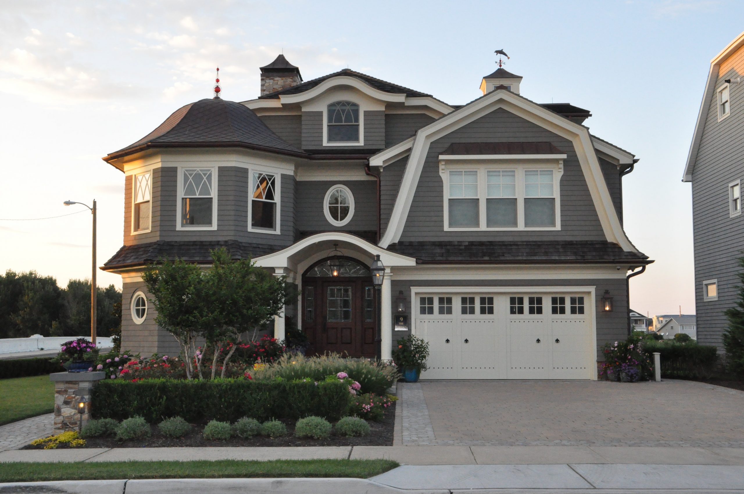 Dark gray cedar shake siding colors with white trim and round columns. Dark brown stained wood front door. White garage doors. Black shingled roof. Brown gutters. Paver walkways and driveway. Beautiful landscaping. Brown stone veneer and matching chimney.