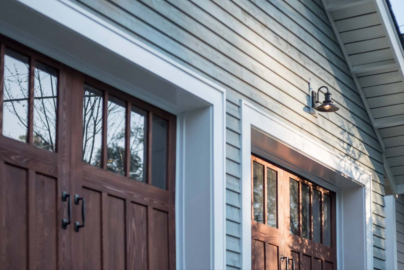 closeup view of garage doors and lap siding wood soffit exterior hardware