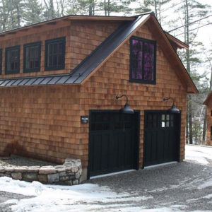 Detached garage design with cedar shake wood siding and black trim. Black garage doors. Black metal roofing.