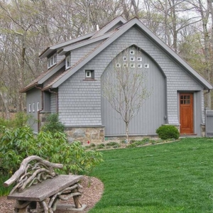 Gray detached garage design with cedar shake wood siding and stained brown real wood door. Real stone veneer.