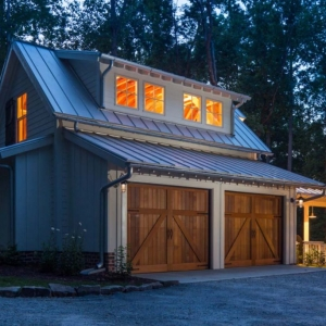 Gray detached two car garage with metal roofing. Stained brown real wood garage doors. Vertical siding. Red brick veneer.