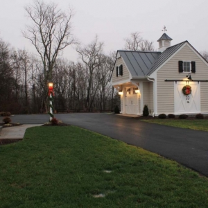 Two car detached garage design with cream colored siding and white doors. Black shutters. Barn doors. Gray metal roofing.