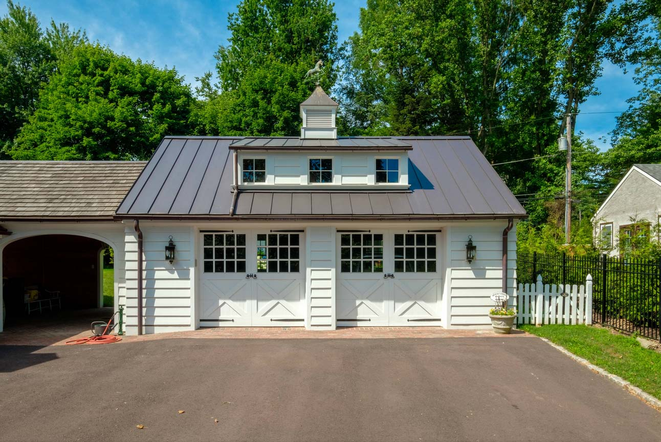 Two car detached garage design with white siding and white door, metal roofing. Living space above. Breezeway. Brown metal gutters.
