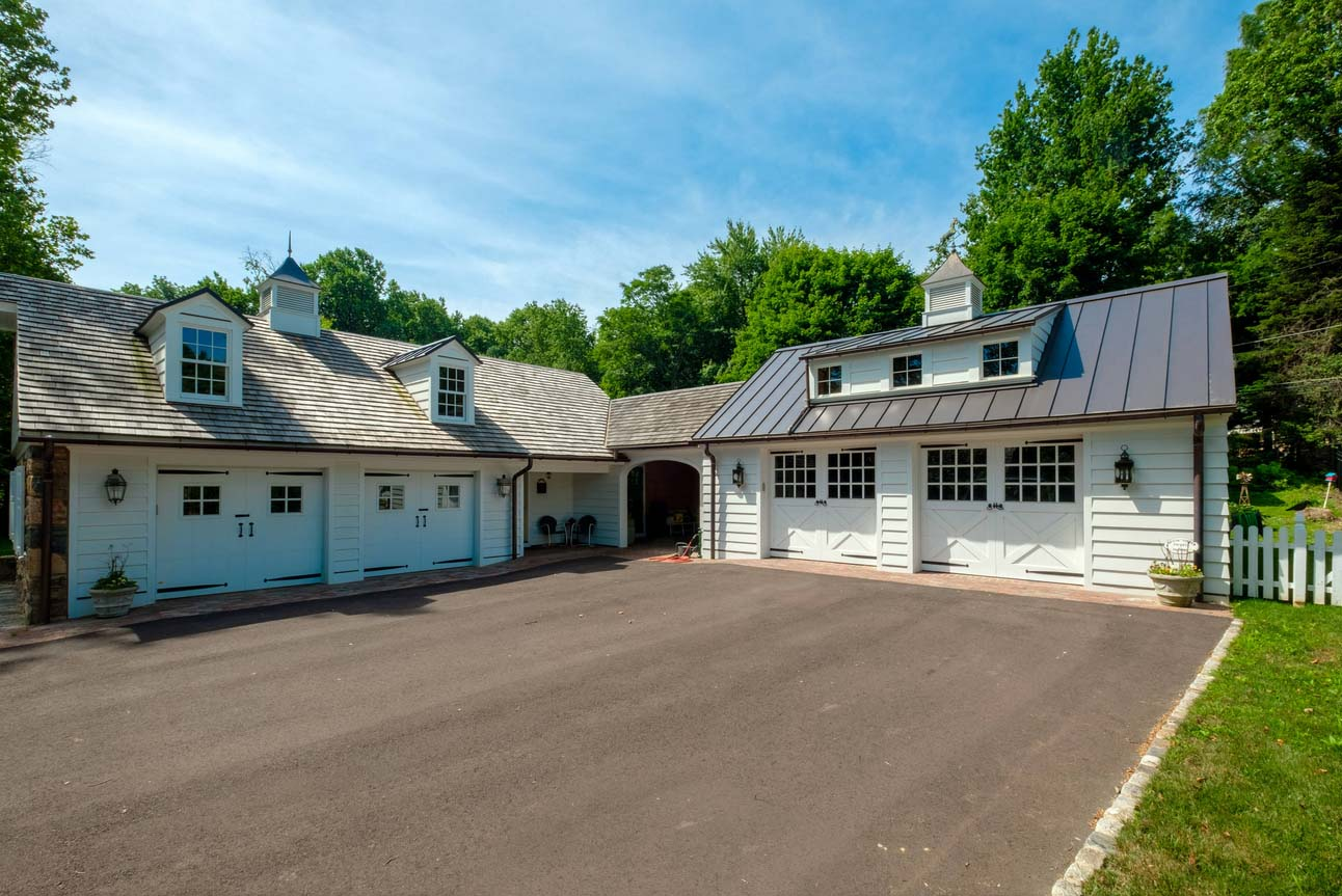 Four car detached garage design with metal roofing and brown shingles. White siding with white doors. Living space above. Breezeway.