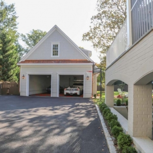Two car detached garage with gray cedar shake vinyl siding. Brass metal accent roofing. Living space above. White trim.