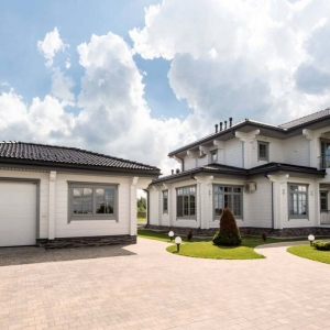 One car detached garage design with living space. Gray trim. Real stone base veneer. Whote horizontal lap siding. Black tile roof.