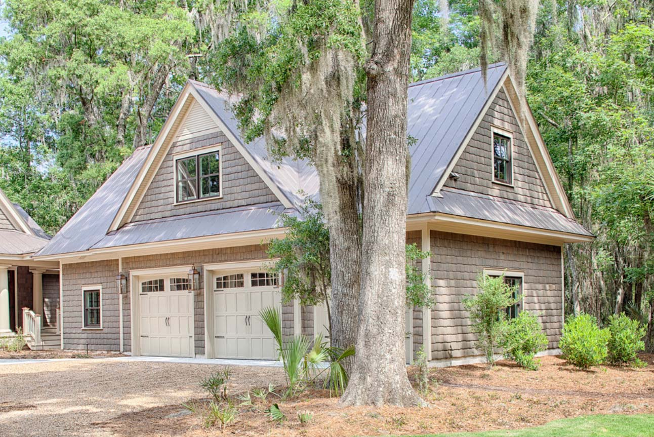 Oversized two car detached garage with living space above and shop. Real wood cedar shake siding with metal roofing. Taupe doors and trim. Black framed windows.
