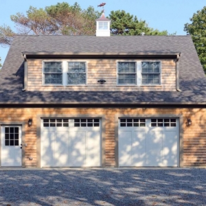 Two car garage design with second floor living space. White doors with gray trim. Real wood cedar shake siding.
