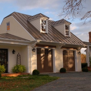 2 Car detached garage design with small 2nd floor room. Cream painted stucco veneer siding with brown doors. Brown metal roof. Small entry room with shop. White columns and trim.