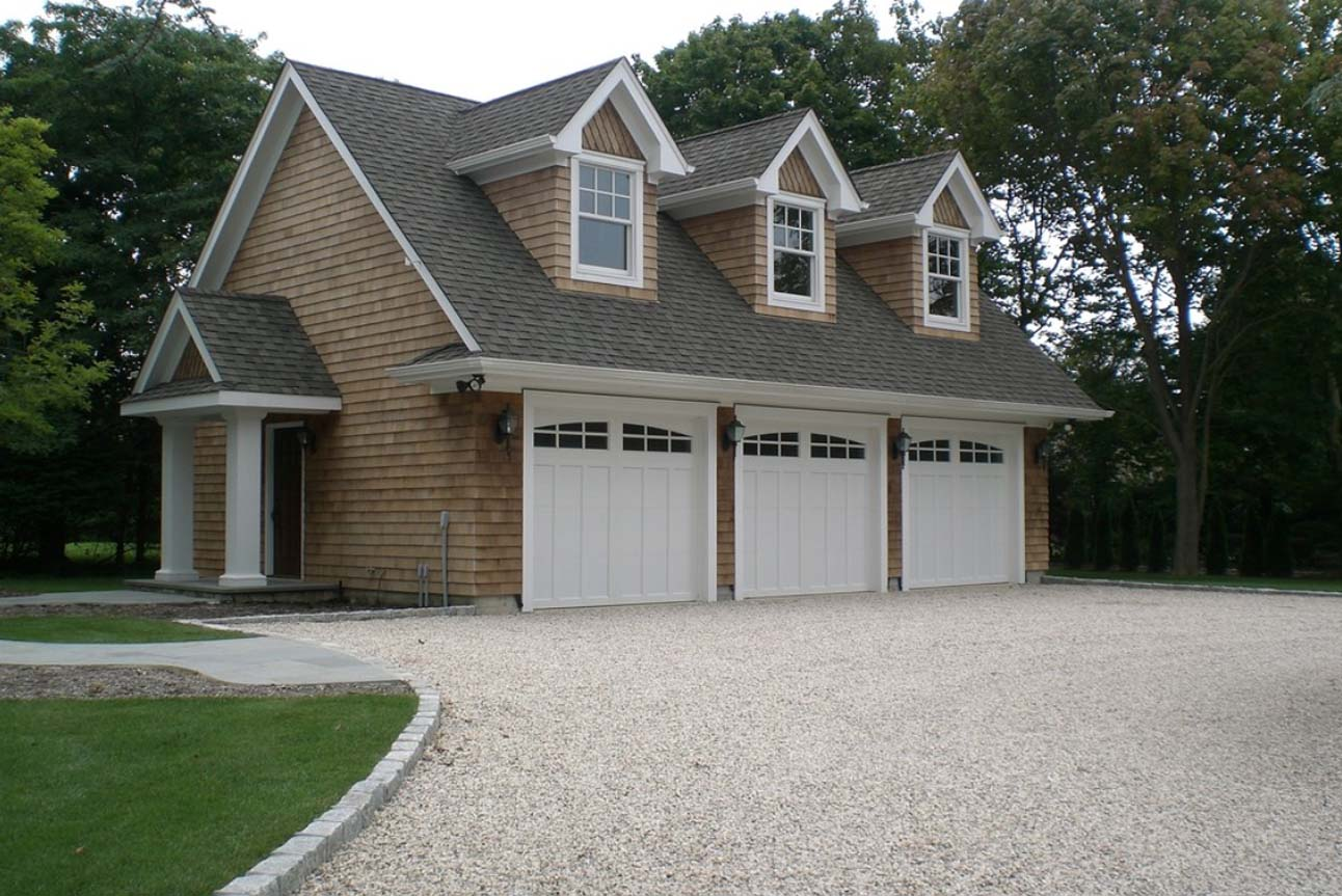 Three car detached garage design. White doors with real wood cedar shake siding. White columns and trim. 2nd Floor living space.