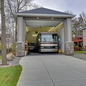 One car oversized garage design. Big enough to fit a bus. Gray cedar shake siding with dark gray trim. Real stone veneer.