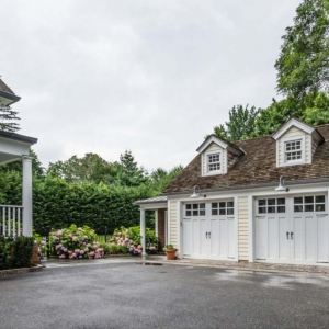 Two car detached garage design with workshop. Cream colored neutral siding with white doors and trim. Brown shingled roof.
