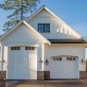 Two car oversized garage. One bay large enough for a bus. White siding and trim with white doors. Red brick veneer. Black framed windows with vertical siding accents.