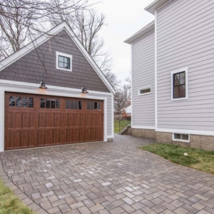 Two car detached garage design with one large door. Two toned gray siding with a stained brown door. Paver driveway. Black framed windows.