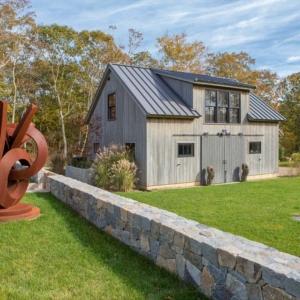 Detached garage design with sliding barn door. Modern style. Vertical real wood siding with black framed windows. Metal roofing.