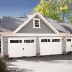 Three car detached garage design with porch. Gray siding with white trim and white garage doors.