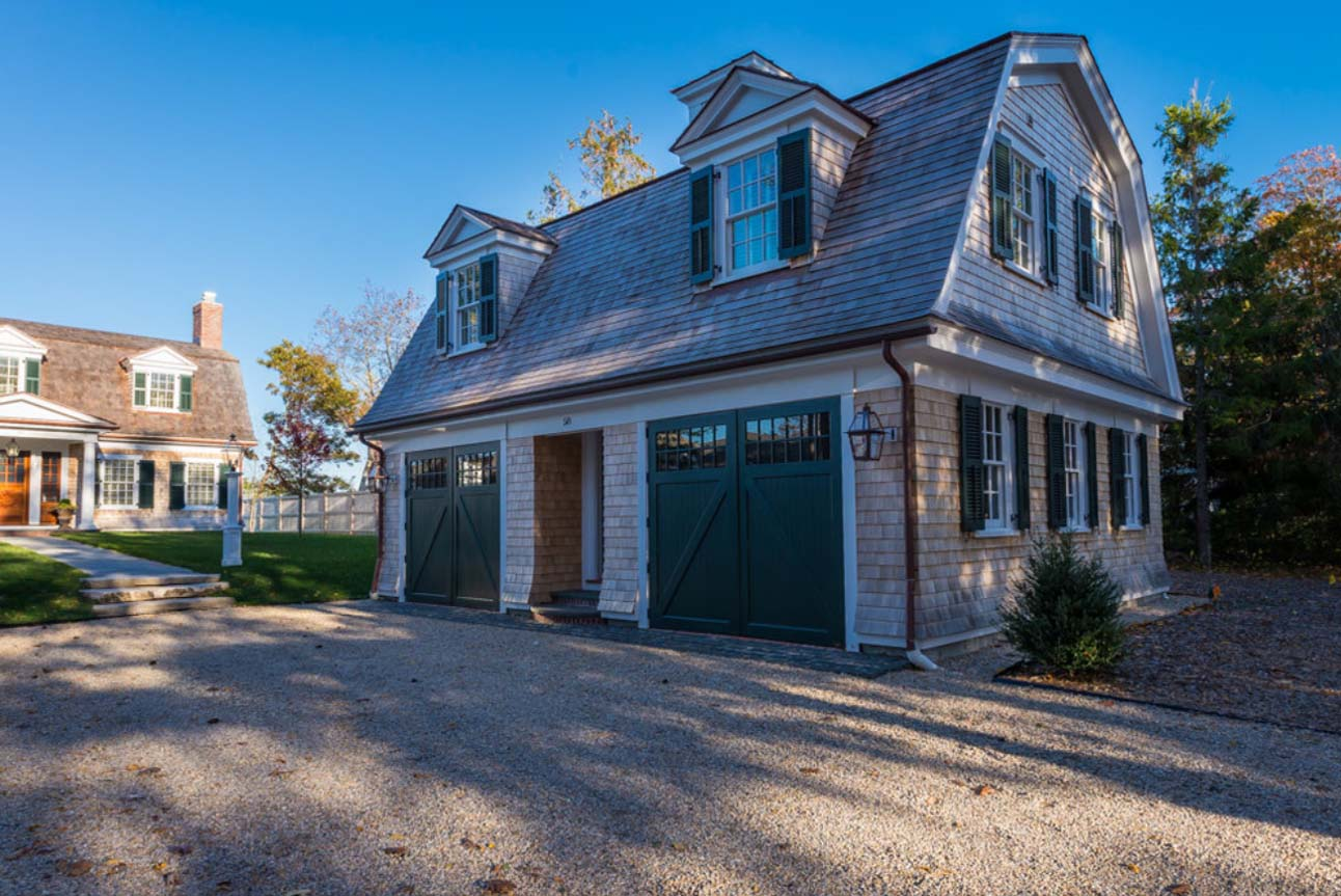 Two car detached garage design with 2nd floor living space apartment. Real wood cedar shake siding and roofing. Green doors with white trim. Matching green shutters. Gambrel roof.