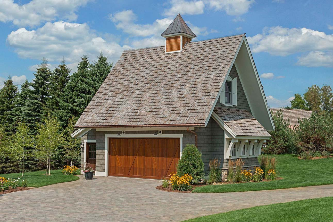 2 Car detached garage with a frame roof design. 2nd Floor living space. Light brown cedar shake siding. Stained brown garage and entry door. White trim and siding accents. Large paver driveway.