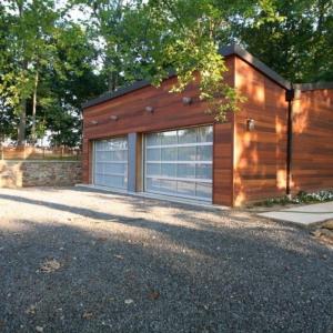 Modern 2 car detached garage design. Ipe wood siding. Black metal roofing and trim. Metal and glass garage doors. Gravel driveway.