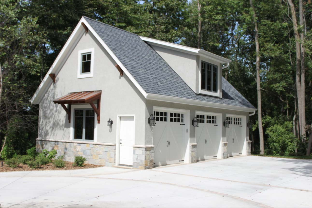 3 Car detached garage design with gray stucco veneer siding and real stone base veneer. White garage doors with white trim. 2nd Floor living space. Brown metal accent roof.