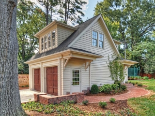 detached garage with beige siding and wood stained doors brick and dormers