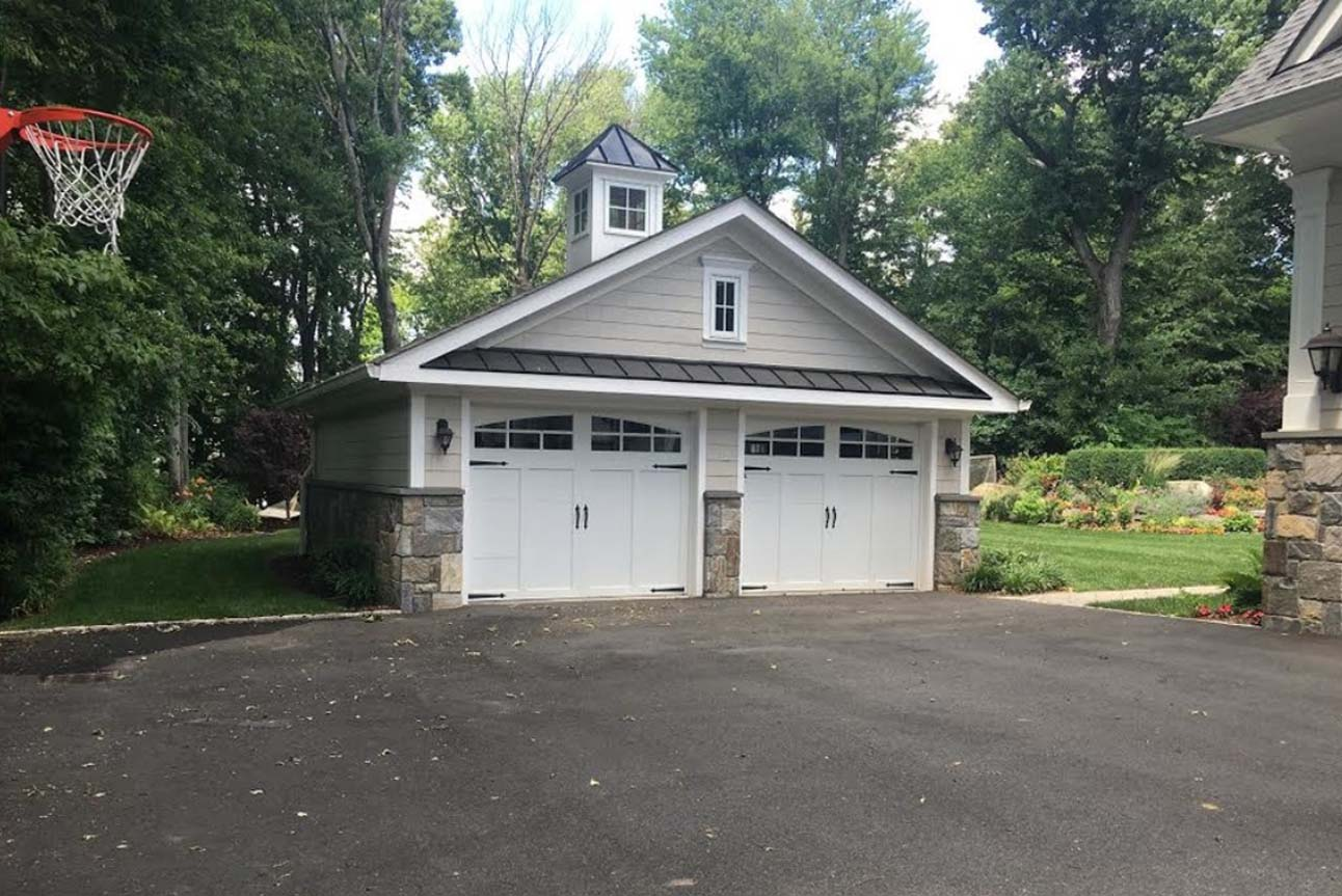 2 Car detached garage design. Light tan siding with white garage doors and real stone veneer. Black metal accent roofing.