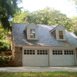 Simple 2 car detached garage design with dormers. Real stone veneer siding with white garage doors. White trim and vinyl siding accents.