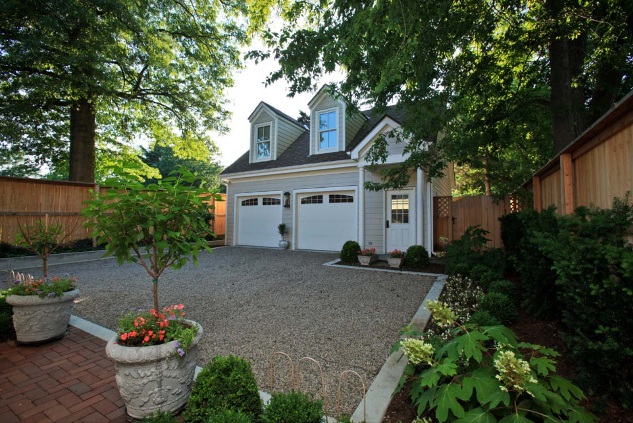 2 Car detached garage design with dormers. White doors with light gray siding and a black shingled roof.