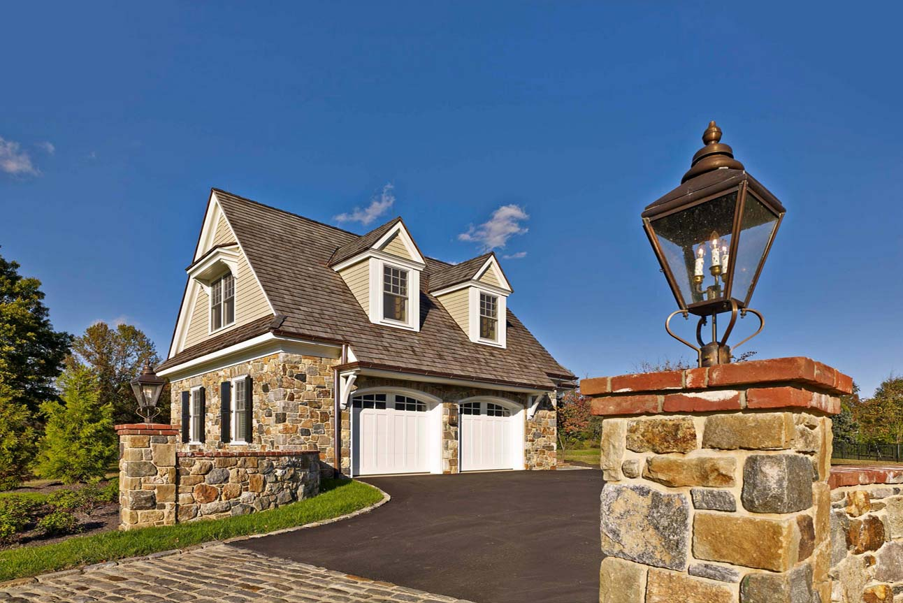 Rustic country detached 2 car garage design. Real stone veneer with beige vinyl siding. Brown shingled roof. White garage doors and trim. Brown gutters. Matching stone retaining walls with a red brick cap.