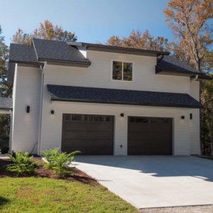 2 Car detached garage with 2nd floor apartment and a modern design. White siding with white tri and dark brown doors. Black gutters with a black roof.