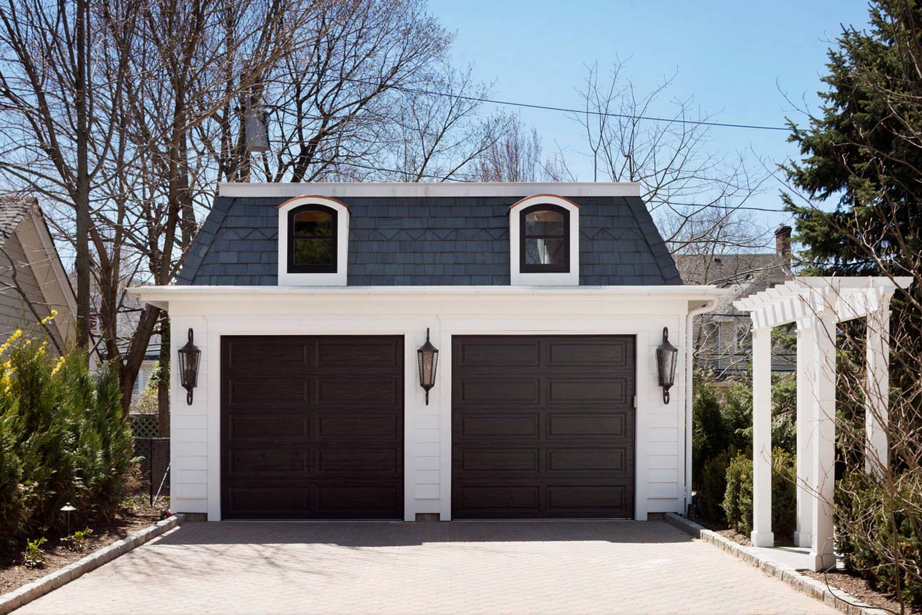 Small 2 car detached garage design. White siding with dark brown doors. Dormers. Blue shingle roof. Black frame windows. Paver driveway.