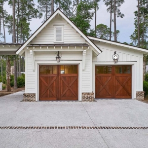2 Car detached garage design with breezeway. Horizontal white lap siding. White trim. Stained brown wood doors. Architectural details. Red brick base veneer. Metal accent roof. Fancy garage design.