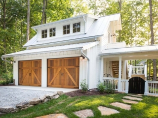 detached garage with white vertical siding wood doors and metal roof with shed dormer