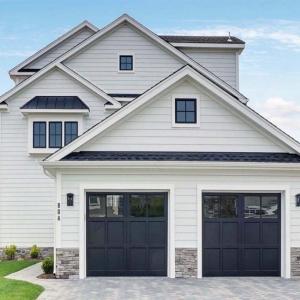 2 Car detached garage design. White horizontal lap siding with black garage doors and black framed windows. Gray stone veneer. Black roofing shingles.