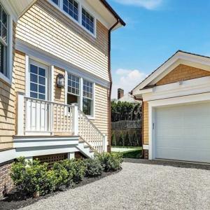 Small one car detached garage. White garage door with yellow siding. Cedar shake siding. Red brick base veneer. Brown gutters.