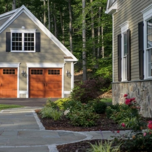 beautiful detached garage with white trim wood doors and lap siding black shutters and dormer