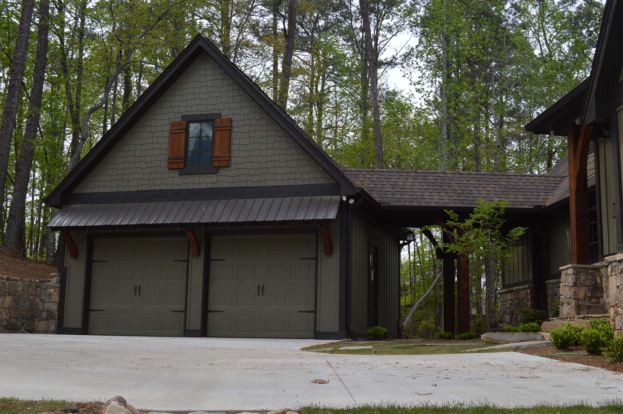 detached garage with breezeway dark siding with metal roof real stone