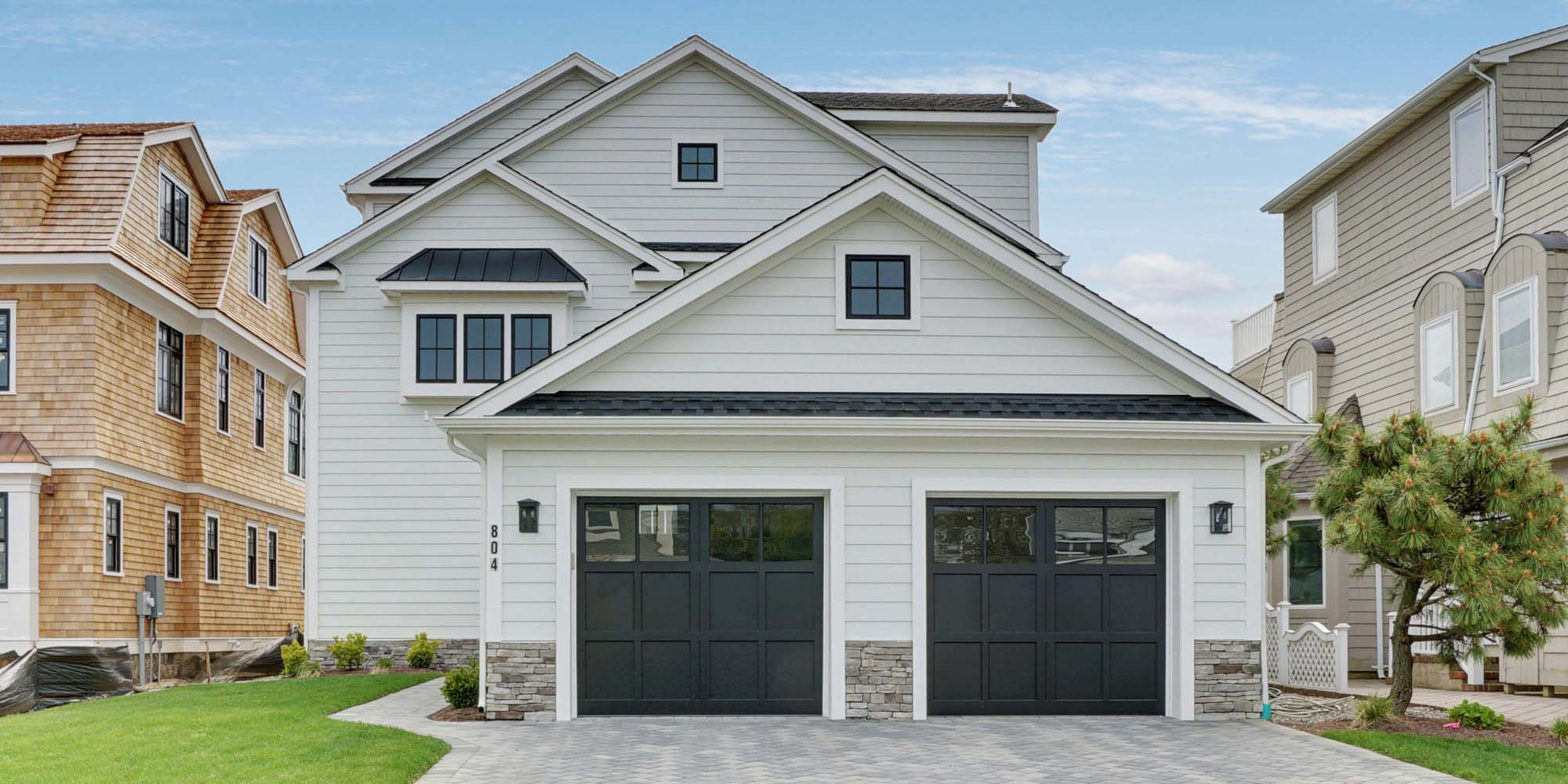 stunning two car detached garage ideas white siding with black garage doors and stone veneer