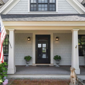 Gray house siding colors with black front door and white trim. White columns. Black framedwindows.