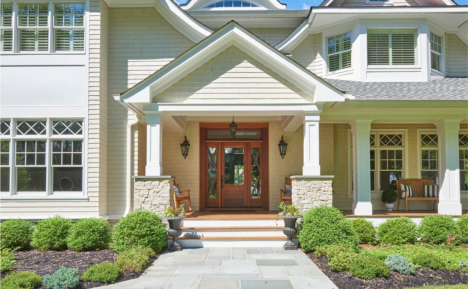 Neutral house siding colors. Light tan with a brown stained wood front door. Light gray stone veneer. White trim. White columns. Blue stone walkway.