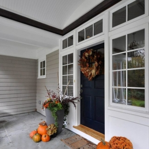 Gray house siding color scheme with dark blue front door. White trim and wall paneling. Blue stone front porch top. White columns.