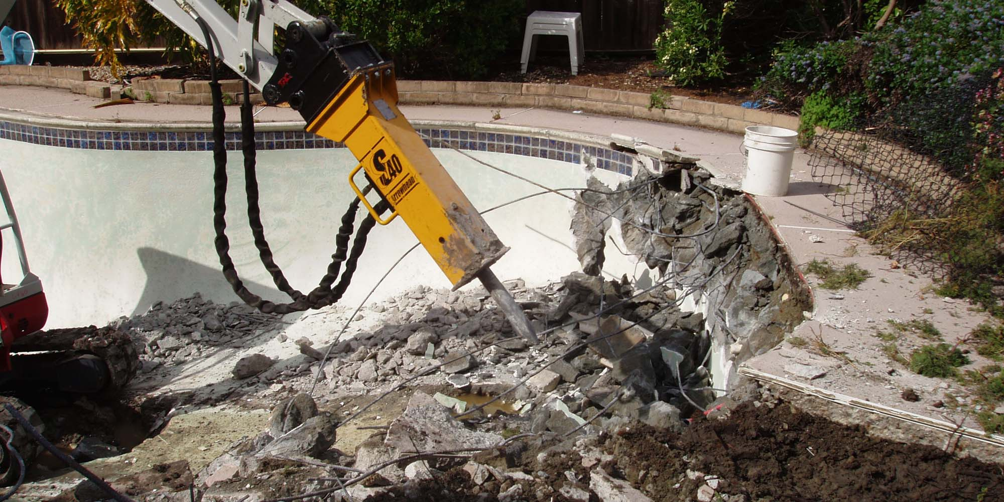 swimming pool removal NJ removing a concrete in ground swimming pool with machinery - Gambrick