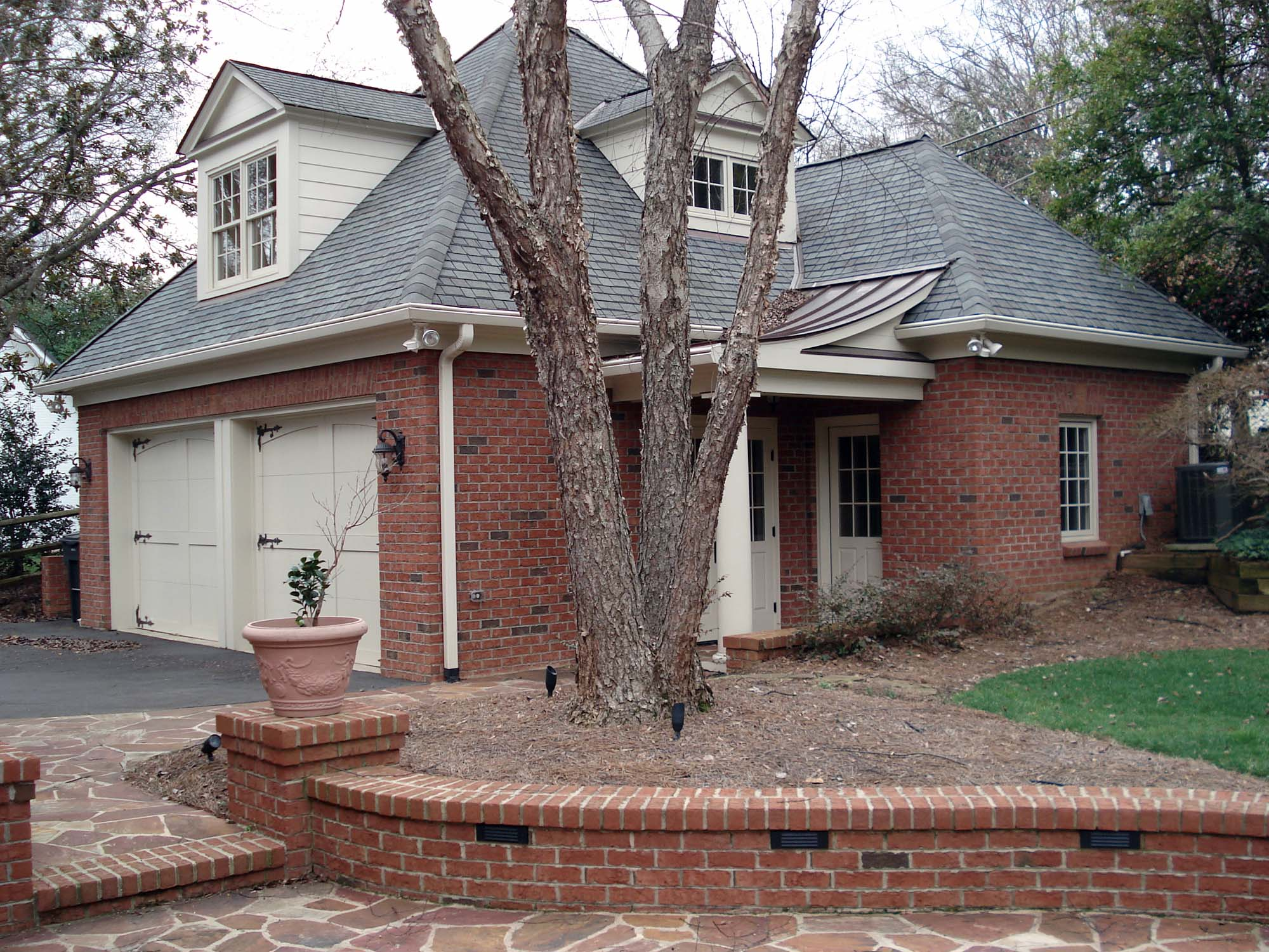 red brick detached garage craftsmen style with cream colored siding