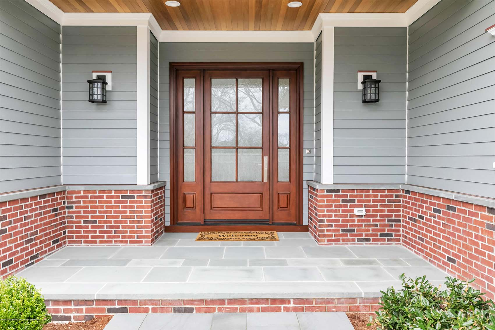 wood front door with glass and transoms gray siding with red brick house and blue stone patio
