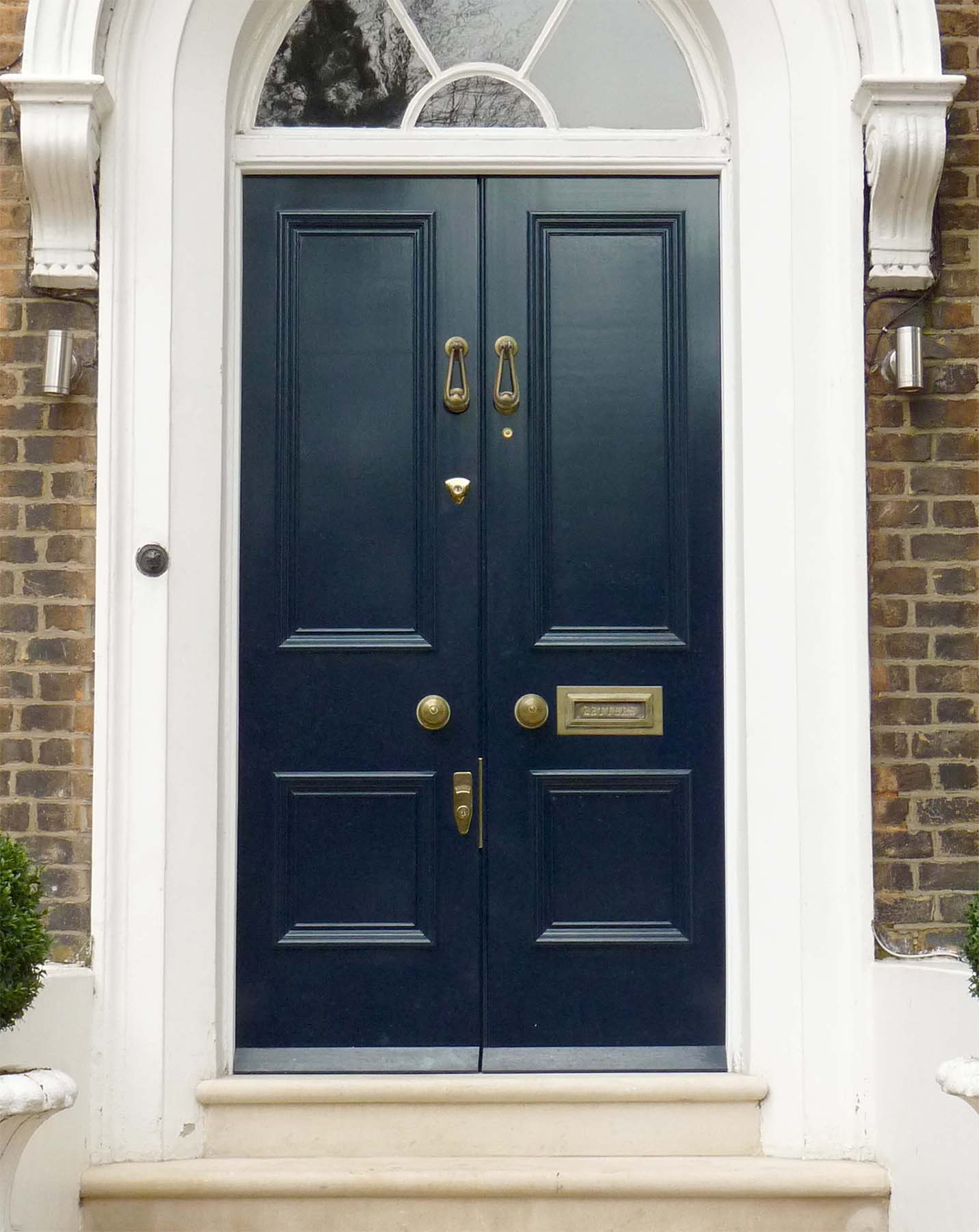 Blue front french door with gold hardware round transom white trim with red brick house