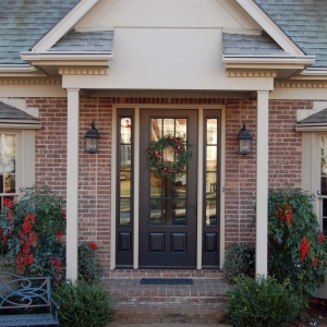 black front door with side transoms tan trim with red brick house