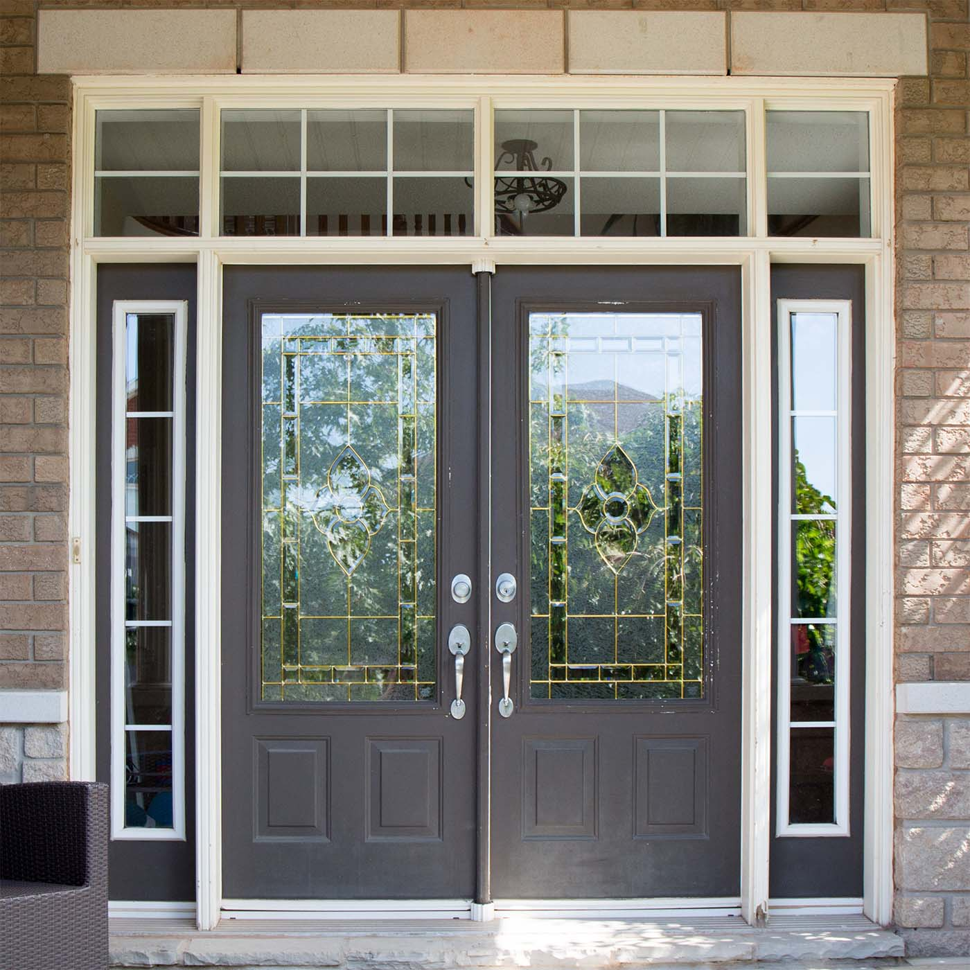 Dark gray french front door with glass stransoms and beige brick house
