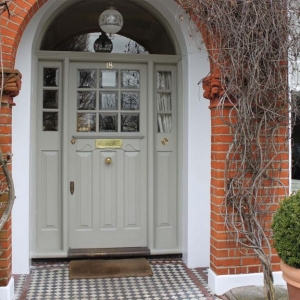 Light gray front door with transoms white trim and red brick house green porch plants vines